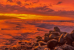 The World on Fire (Daniel P Froese) Tags: dunedin new zealand clair beach ocean waves sunrise dawn photo image picture photos images pictures reflection red rocks surf fire sky oceanview world flame flaming seascape otago