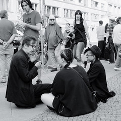 Their guardian angels disapprove (Time.Captured.) Tags: street friends people bw berlin angel square fuji place pavement cigarette candid platz smoke group citylife streetphotography 11 smoking squareformat sw rest engel freunde gruppe powwow x100 bsquare fujix100