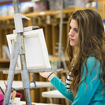 A student painting a canvas during an art class.