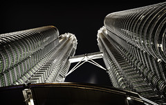 Looking up at the Petronas Towers (jbovay) Tags: kualalumpur petronastowers view lookingup blackandwhite fromthebottom skyscraper bridge nightime scale size bandw skyscape night emptyspace travel malaysia