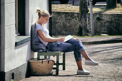 Taking a brake (Dannis van der Heiden) Tags: girl sitting relax puzzle pen street cobbles house bag bench jeans sneakers tail cushion sunlight amersfoort earrings beauty quai slta58 sigma18300mm netherlands cup relaxing writing persona portrait zoom headphone