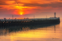 Golden sunset . (rudi.verschoren) Tags: nieuwpoort outdoor old colors tall pier artistic zonsondergang sunset sky seascape reflection reflectie red yellow argenta blue people light lines lights lighthouse water sea seaside glow golden geel rood sun dusk eos europe europa exposure evening flanders belgium westvlaanderen mood fog nature ngc overlooking panorama paars purple pittoresk port