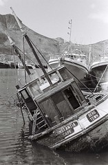 Nautical Decay, Hout Bay Harbour (Peter Nichol) Tags: pentaxmx ilforddelta400 film filmphotography analogue blackandwhite houtbay fisherman fishingboat captain monochrome nauticaldecay sinking wreck capetown ishootwithfilm filmisnotdead