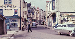 Sidmouth (M C Smith) Tags: buildings shops sky road pavement cars coach parking signs people crossing shelter blue white