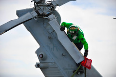 A Sailor fits a cover over a helicopter tail rotor. (Official U.S. Navy Imagery) Tags: unitedstates sandiego calif
