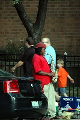 He plays a mean sax even got the kid's attention. (kennethkonica) Tags: blue red people music orange white men brick cars fence nikon midwest traffic indianapolis hats indiana nikond70s sax blackmen redwhiteblue musicalinstruments