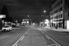 Hawthorne Blvd. (Curtis Gregory Perry) Tags: portland oregon hawthorne night pdx longexposure black white bw monochrome street road building car nikon d810 line lane stripe paint median middle 50mm f12 volkswagen streetlight power