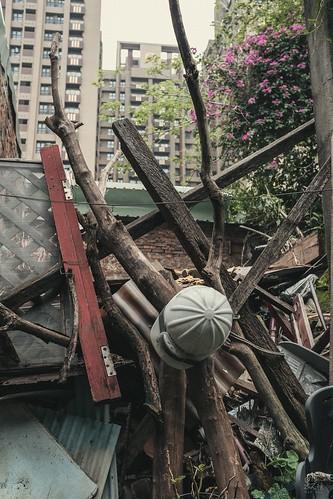 剛落成的大樓,而他背後的老街雖然有些還有人住,但也看到好幾間長滿蚊蟲的廢墟。