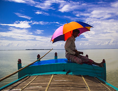 Under the blue sky and the colored umbrella (Hermaenos) Tags: color canon boatman 60d vftw