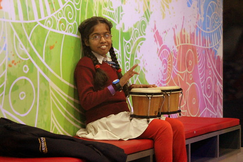 A happy little girl enjoying playing with the musical instruments at KidZania.