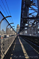 Walk across Sydney Harbour Bridge (Kaye Menner) Tags: blue sky sunlight black building architecture fence wire construction arch sydney fences bluesky pylon walkway barbedwire harbourbridge pathway sydneyharbourbridge cityview sunspots bridgeconstruction skybackground wirefences bridgepylon sydneycityview sydneyicon kayemennerphotography kayemenner kayemennerlandscape kayemennerarchitecture walkacrosssydneyharbourbridge walkwayacrosssydneyharbourbridge sunlightmarkings