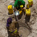 Women Taking Drinking Water From A Well Hole In The Sand And Pouring It Into Plastic Containers, Lasadacwo Village, Somaliland