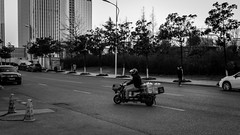 Thirsty man (Go-tea 郭天) Tags: man driver driving movement motorbike motobike delivery duty business job deliver delivering ride riding light helmet cars buildings road protection protected safety water bottles pollution polluted trees drink drinkable thirsty supply sypplier health healthy electric qingdao huangdao street urban city outside outdoor people bw bnw black white blackwhite blackandwhite monochrome asia asian china chinese shandong canon eos 100d 24mm prime