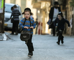 'Miracles Happen. Believe!' (ybiberman) Tags: israel jerusalem kippah meahshearim tzitzit boys candid children foodbag kindergarten running streetphotography tongue