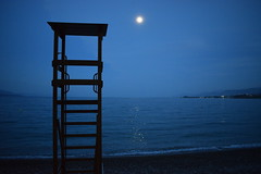 Day 100: Is for... The Night Guard (Konstantinos Karnaros) Tags: night guard lifeguard sea fullmoon moon blue beach greece 365
