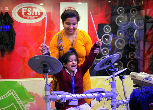 KidZania Tour for Kids with disabilities: The little rockstar playing on drums.