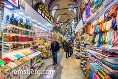 Shoppers walk by scarves and a small food market at the Grand Bazaar in Istanbul, Turkey, one of the country's most visited landmarks and oldest public markets. (Remsberg Photos) Tags: istanbul turkey grandbazaar bazaar shopping commerce covered goods forsale products food assortment items nuts traditional scarves browse walking choose tur