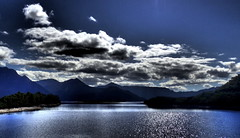 Moody LAKE BURBURY (Lani Elliott) Tags: nature naturephotography water lake lakeburbury glistening shimmering light blue moody mountains mountainrange australia tasmania queenstown sky skies cloud clouds bluesky