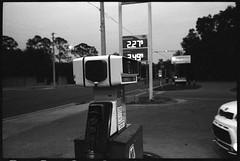 At the pump (FreezerOfPhotons) Tags: leica m5 leicam5 cosinavoigtlandernokton40mmf14sc singlecoatedlens nokton40mm14sc xtol ilfordsurveillancefilm400iso ilfordp3 dark lowlight twilight fuelpump sign road poles wires