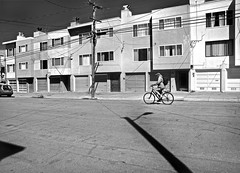 Irving Street, Outer Sunset - San Francisco, CA (Rex Mandel) Tags: bicycle bicyclist blackandwhite bw monochrome apartments sanfrancisco sf sunsetdistrict outersunsetdistrict telephonewires telephonepole highcontrast shadow citystreet