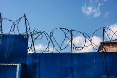 Blue on blue (ideal_farm) Tags: blue barbed wire fence factory sky border bricks sony alpha a65 minolta freedom