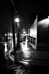 A Rainy Night in St. John's 2 (LongInt57) Tags: city street sidewalk streetlights lights building night raining rainy rain wet town stjohns saintjohns newfoundland canada bw monochrome black white grey gray motion blur cars vehicles