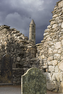 Irish ruins at Glendalough, stone walls, tombstomes, and round tower with dark stormy sky