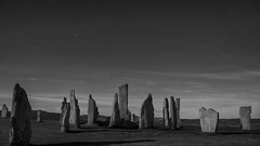petrified mummers in their eternal, nightly dance (lunaryuna) Tags: scotland outerhebrides isleoflewisandharris callanaisstandingstones callanish megaliths stonecircle night nightphotography nocturnalphotography nightsky starrynight starslikedust blackwhite bw monochrome lunaryuna bronzeageheritage ngc