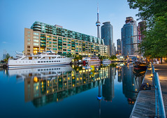 Toronto Harbor Reflection (`James Wheeler) Tags: life city travel red vacation white holiday toronto ontario canada tree tower tourism nature water sport skyline architecture night cn buildings landscape lights harbor boat ship cntower waterfront harbour yacht outdoor dusk rail nobody landmark fortune business national metropolis leisure condos luxury wealth torontoharbour