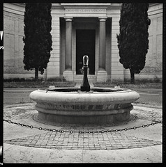 Verano #6, Rome, Italy, 2017 (Giovanni Marasco) Tags: cimiterodelverano cimitero cimiteromonumentaledelverano roma bw bergger berggerpancro400 blackandwhite bn pancro400 kodakhc110dilb rolleiflex planar35f veranocemetery theverano communalmonumentalcemeteryofcampoverano biancoenero zeiss cypresses cypresstrees water fountain statue porta door composition architecture
