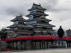 The castle and myself (_Hadock_) Tags: matsumoto castle panorama pano castillo panoramic pannorama pannoramic merge reflection reflect mirror espejo reflejo cityscape citiscape water agua creative commons comons full hd fondo de pantalla screensaver desktop wallpaper free travel holiday viajes viajar destino japon japan old architecture arquitectura nikon d750 tamron 2470 f28 man standing back coat dark grey bridge red
