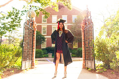 Power Stance (sweeneybrandon) Tags: dress black hair brown graduation uga universityofgeorgia athens college green gate jewelry gold foliage portrait portraiture naturallight red cap gown brick metal bokeh