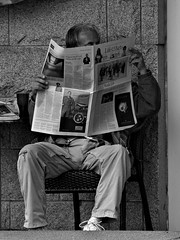 Sunday Morning Paper and Coffee (dons projects) Tags: city autumn blackandwhite bw canada vancouver reading newspaper chair downtown bc candid streetscene olympus canadian photowalk resting zuiko vancouverbc 2012 cityscene evolt e500 zd fourthirds 40150mm photoscape seeninvancouver donsprojects