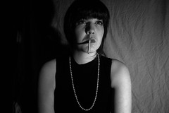 Film noir (Beckyoung) Tags: lighting portrait blackandwhite en white selfportrait black film girl make up set swansea self canon hair noir shadows makeup fringe scene pearls smoking bangs dslr mis filmnoir 1000d