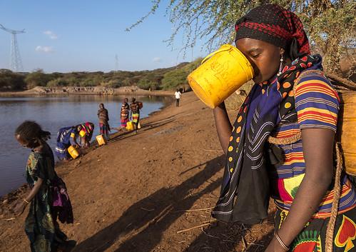 Borana tribe woman drinking water taken from a reservoir
