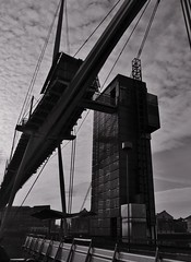 The Crossing (Compactman) Tags: london docks bridge royalvictoria thames excel blackandwhite bw monochrome tower clouds contrast wires docklands panasonic lumix g7