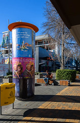 Enjoying the Sunshine (Jocey K) Tags: newzealand southisland canterbury christchurch buildings architecture rebuild trees shadows construction crane sky cbd bollard posters people bin mall flag