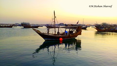 A Fishing Boat (M.RISHAN SHAREEF) Tags: nature blue black beach boat culture evening earth enjoy yellow sea people peoples thenature sky lighting light man night orange ocean qatar red sun water