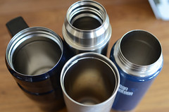 stainless steel metal mugs on table (yourbestdigs) Tags: water bottle travel mug coffee thermos hot drink drinks beverage bottles mugs office leak stainless steel insulated warm liquid food lid lids wood desk table dining tea hydration morning breakfast drinking exercising