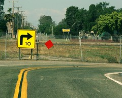 Corner (Boyce Duprey) Tags: 10 flickrfriday corner hanford california bend righthand road sign yellow red diamond fence airport