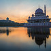 Beautiful Sunrise over a Mosque by the lake with colorful clouds and reflection.