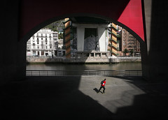 flashes of red (Dave_Davies) Tags: bilbao spain candid street red colour skater skating bridge guggenheim museum river shadow light