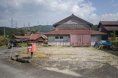 Post, used container, community center. (Yasuyuki Oomagari) Tags: pink post rural country countryside village peace street surface composition nikon d810 zeiss distagont225 wooden ngc
