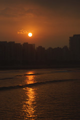 Reflexo (Thiago Souto) Tags: ocean morning sea brazil sky orange costa sun sunlight sol brasil sunrise buildings coast mar sony laranja cu sp santos shore alpha litoral amanhecer prdios oceano a77 nascerdosol  baixadasantista josmenino luzdosol quebramar emissriosubmarino raiosdosol 77
