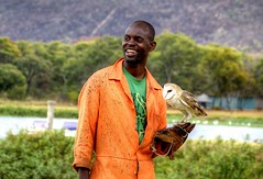 Owl Man (Elena Kis) Tags: africa trees wild portrait people orange white man tree men guy green nature water smile look grass rural landscape nikon shot wildlife happiness owl zimbabwe colourful nikond3200 chivero africanlife tshorts