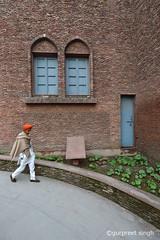 a boy at Jallian wala bagh, Amritsar, IN (gurpreet_singh.) Tags: door travel boy india window wall walking nikon bricks shawl sikh bagh wala d4 jalian nanakshahi