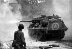 A U.S. M10 tank destroyer firing its gun in the area of Saint-Lô.