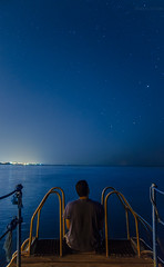 The search (Sherif Wagih) Tags: ocean red sea vacation sky holiday man reflection male night photoshop stars typography lights pier dock nikon long exposure thought sitting peace adult space young egypt tranquility el images tourist east cairo egyptian thinking getty middle dslr sheikh sharm sherif contemplation lightroom amatuer thefinalfrontier curator flickrfriday photogher wagih d5100 gettyimagesmiddleeast