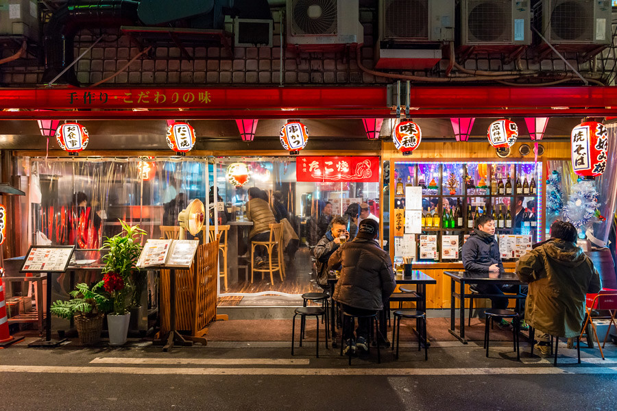 Locals eat and drink late at night at a neighbourhood restaurant