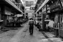 Follow me in the hood (Go-tea 郭天) Tags: hood man old cold winter walk walking back backside qingdao huangdao movement market shops business trade narrow alley atmosphere special specific traditional dirty mess messy perspective follow following umbrella van tables commercial zone area closed hat coat alone lonely street urban city outside outdoor people bw bnw black white blackwhite blackandwhite monochrome asia asian china chinese shandong canon eos 100d 24mm prime